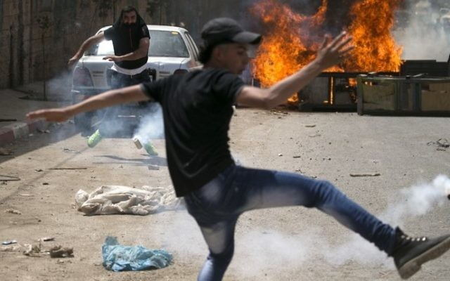 A Palestinian protester dodges teargas cannisters during clashes with Israeli forces in the West Bank village of Beita, southeast of Nablus city, after a protest took place following Friday prayers in solidarity with Palestinian prisoners on hunger strike in Israeli jails, on April 21, 2017. (AFP/ Jaafar Ashtiyeh)