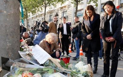 Mayor of Paris Anne Hidalgo (2R) and the Mayor of the 8th arrondissement of Paris Jeanne D'hauteserre (R) stand as they pay their respect at the site of a shooting on the Champs-Elysees in Paris on April 21, 2017, a day after a gunman opened fire on police along the avenue, killing a policeman and wounding two others. (AFP/Francois Guillot)