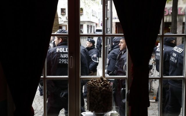 Policer officers are seen through a window during a protest against the party congress of Germany's right-wing populist Alternative for Germany (AfD) in Cologne, western Germany, on April 22, 2017.  (AFP  / Odd ANDERSEN)