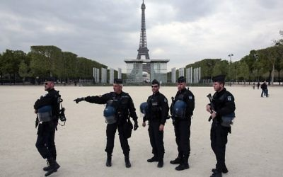 French policemen stand in front of the Eiffel tower in Paris on April 22, 2017. (AFP/Geoffroy van der Hasselt)