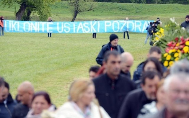 Activists hold a banner reading 'Remove the Plaque' as Croatian Prime Minister Andrej Plenkovic (C,R) walks during a ceremony honoring the victims of its most brutal World War II death camp in Jasenovac, on April, 23, 2017. (AFP/STRINGER)