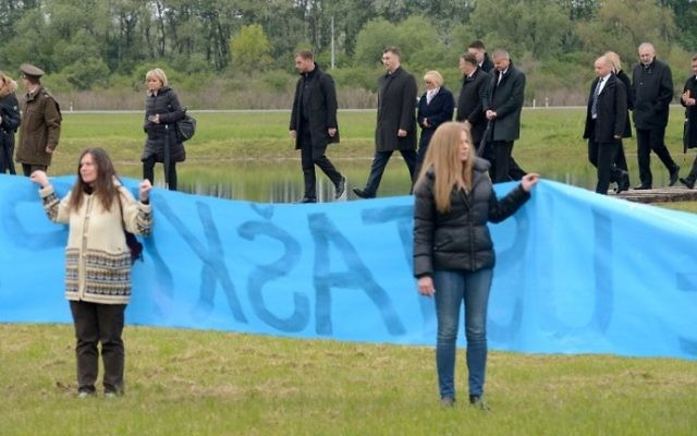 Activists hold a banner reading 'Remove the Plaque' as Croatian Prime Minister Andrej Plenkovic walks during a ceremony honoring the victims of its most brutal World War II death camp in Jasenovac, on April 23, 2017. (AFP/STRINGER)