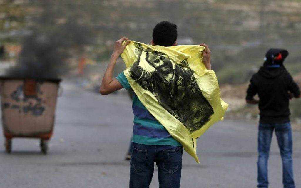 A Palestinian demonstrator holds a flag bearing an image of Marwan Barghouti during a protest near the West Bank settlement of Beit El, north of Ramallah on April 23, 2017. (AFP Photo/Abbas Momani)