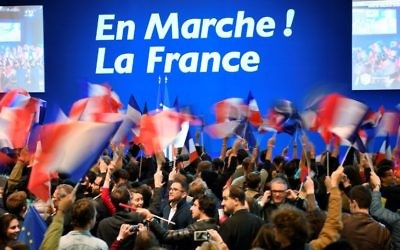 People wave French national flags before a meeting of French presidential election candidate for the En Marche! movement at the Parc des Expositions in Paris, on April 23, 2017, during the first round of the Presidential election. (Eric Feferberg/AFP)