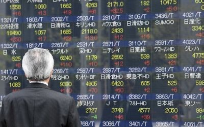 A businessman looks at an electronic share indicator at the window of a securities company in Tokyo on April 24, 2017. (AFP PHOTO / Toshifumi KITAMURA)