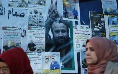 Palestinian women walk past a wall bearing posters, including a portrait of prominent prisoner Marwan Barghouti, during a rally in Ramallah, in support of him and other prisoners on hunger strike in Israeli jails on April 24, 2017. (AFP/Abbas Momani)