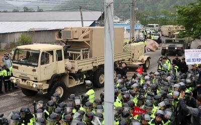 Protesters and police stand by as trailers carrying US THAAD missile defence equipment enter a deployment site in Seongju on April 26, 2017. (AFP Photo/YONHAP)