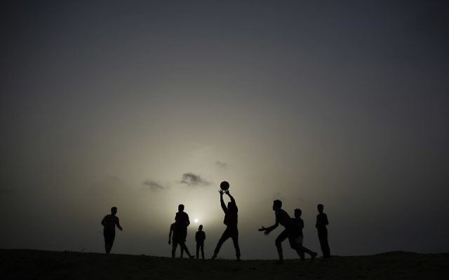 Palestinian youths play volleyball as the sun sets in Gaza City, on April 26, 2017. / AFP PHOTO / MOHAMMED ABED