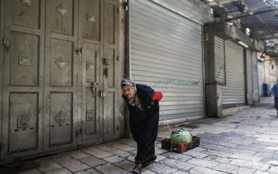 An elderly woman pulls a makeshift cardboard cart past a closed shop in the Old City of Jerusalem on April 27, 2017, during a trade strike in support of Palestinian prisoners on hunger strike in Israeli jails. (Ahmad Gharabli/AFP)