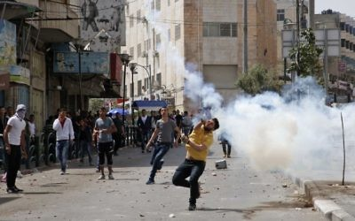 Palestinian protesters throw stones in the West Bank city of Hebron on April 27, 2017, during clashes with Israeli soldiers as a trade strike in support of Palestinian prisoners on hunger strike in Israeli jails takes place. (AFP/Hazem Bader)