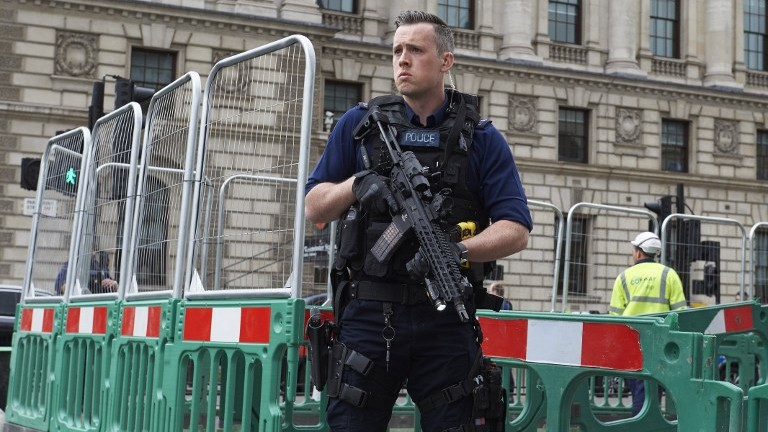 A British police officer stands guard near the Houses of Parliament in central London on April 27, 2017. near where a man was detained and taken away by police. (AFP Photo/Niklas Halle'n)