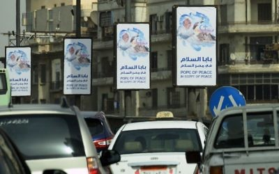 Cars drive past welcome banners bearing a portrait of Pope Francis a day ahead of his visit to the capital Cairo, on April 27, 2017. (AFP/Mohamed El-Shahed)