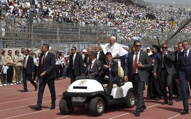 Pope Francis is surrounded by security as he rides an uncovered Popemobile before the start of a mass on April 29, 2017 at a stadium in Cairo. (AFP PHOTO / Andreas SOLARO)
