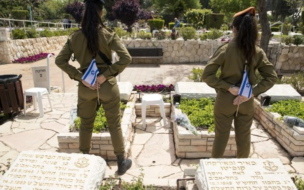 Israeli soldiers carrying the flag stand at attention at the graves of killed comrades at the Kiryat Shaul military cemetery as the country starts to mark the memorial day for fallen soldiers in Tel Aviv on April 30, 2017. (AFP PHOTO / JACK GUEZ)