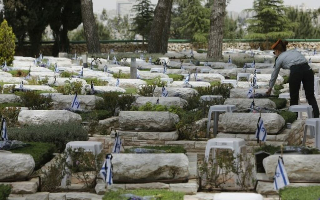 An Israeli soldier lays flowers on the graves of fallen soldiers at the Mount Herzl military cemetery in Jerusalem on April 30, 2017, a few hours ahead of the start of Remembrance Day, commemorating fallen Israeli soldiers. (AFP PHOTO / MENAHEM KAHANA)