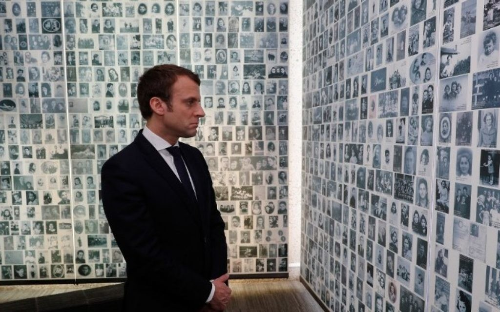 French presidential candidate Emmanuel Macron looks at some of the 2,500 photographs of young Jews deported from France during the WWII Nazi occupation, during a visit to the Shoah Memorial on April 30, 2017 in Paris. (AFP PHOTO / POOL / PHILIPPE WOJAZER)