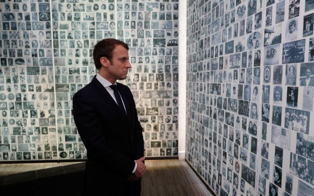 French presidential election candidate for the En Marche! movement Emmanuel Macron  looks at some of the 2,500 photographs of young Jews deported from France during the WWII Nazi occupation, during a visit to the Shoah Memorial on April 30, 2017 in Paris. (AFP/Pool/Philippe Wojazer)
