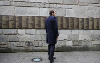 French presidential election candidate for the En-Marche movement, Emmanuel Macron stands at the Wall of the Rigtheous (Le Mur des Justes) during a visit to the Shoah Memorial on April 30, 2017 in Paris. (AFP PHOTO / POOL / PHILIPPE WOJAZER)