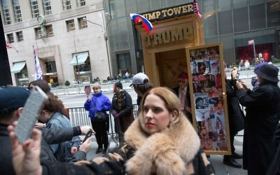 A woman takes a selfie with an outhouse featuring a Trump doll sitting on the toilet in front of Trump Tower in New York during an April Fool's Day event on April 1, 2017 (Kevin Hagen/Getty Images/AFP)