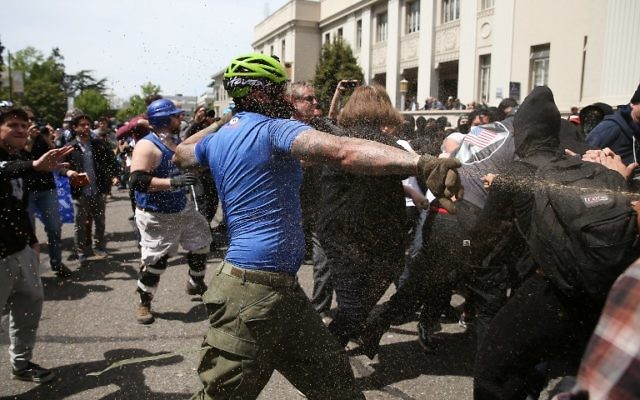 """A Trump supporter runs at protesters while being pepper sprayed at a """"Patriots Day"""" free speech rally on April 15, 2017 in Berkeley, California. (Elijah Nouvelage/Getty Images/AFP)"""