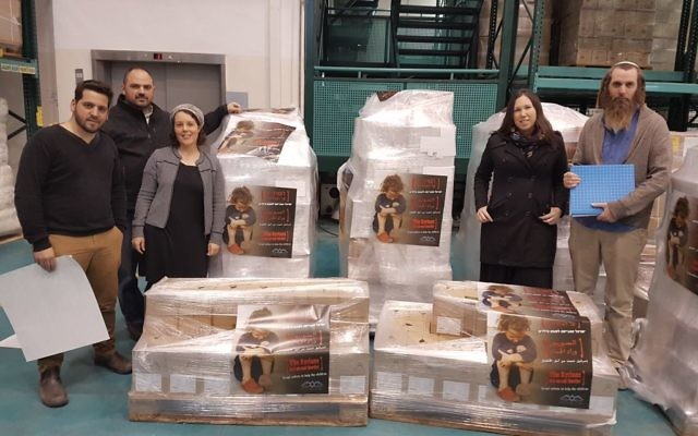 Leaders from the Just Beyond our Border campaign stand next to boxes of aid that were shipped off to Syria. (Courtesy)