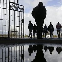 People enter the Sachsenhausen Nazi death camp through the gate with the inscription 'Arbeit macht frei' (work sets you free) for commemorations for the 72nd anniversary of the liberation of the camp in Oranienburg, about 35 kilometer north of Berlin, April 23, 2017. (AP/Markus Schreiber)