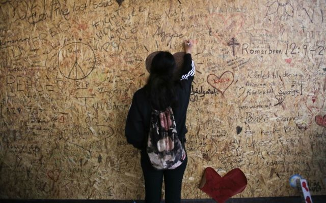 A woman writes a message on a wooden plank at the department store Ahlens in Stockholm, Sweden, Sunday, April 9, 2017, the site of an apparent terror attack the previous Friday. (AP Photo/Markus Schreiber)