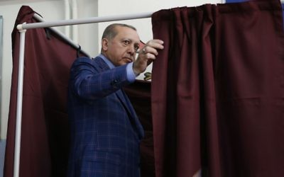 Turkey's President Recep Tayyip Erdogan enters a voting booth inside a polling station in Istanbul, Turkey, on Sunday, April 16, 2017.  (AP/Lefteris Pitarakis)
