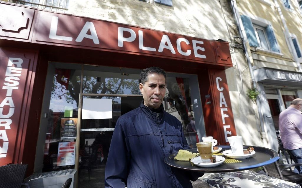 """Mohamed Zhani, stands outside his cafe restaurant """"La Place"""" in Beaucaire, southern France, on Tuesday April 4, 2017. (AP Photo/Claude Paris)"""