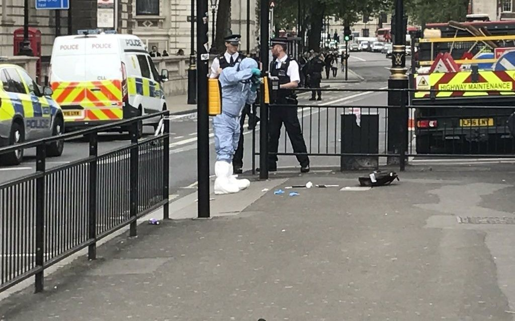 Police photograph items on the pavement in Whitehall, London, Thursday April 27, 2017, after a man was arrested by police. London police say they have arrested a man for possession of offensive weapons near Britain's Houses of Parliament. (Ross Kempsell‏ via AP)