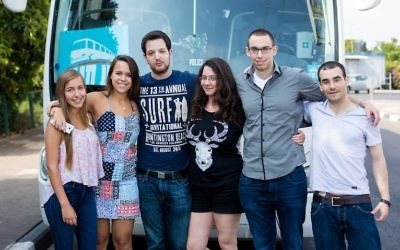 Noa Tnua founder Roy Schwartz Tichon, second from right, and board member Noam Tel-Verem, third from right, posing with volunteers before the launch of their bus service in Ramat Gan, Israel, June 6, 2015. (Avihai Levy)