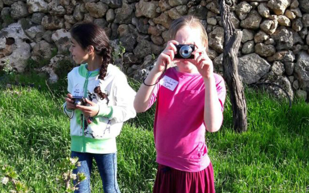 Young Israeli and Palestinian girls take photos together in Ard, as part of the Roots coexistence initiative. (Brett Kline/Times of Israel)