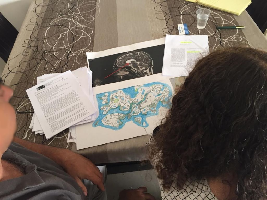 G and S, the parents of alleged bomb hoaxer M, at their home in Ashkelon, with medical documents, one of the maps drawn by M, and an MRI of his brain, on the table in front of them, April 26, 2017 (DH/Times of Israel staff)
