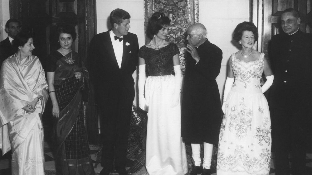 A dinner at the Indian Embassy in Washington DC. (L-R): Shobha Nehru; Indira Gandhi; US president Kennedy; first lady Jacqueline Kennedy; Indian prime minister Jawaharlal Nehru; Rose Kennedy; and Indian ambassador BK Nehru. (Public domain, White House, Wikimedia Commons)