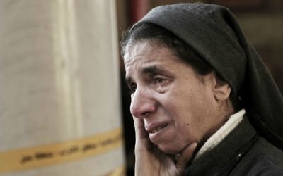 In this Dec. 11, 2016 file photo, an Egyptian Coptic nun weeps as she looks at damage inside the St. Mark Cathedral in central Cairo, following a bombing. (AP Photo/Nariman El-Mofty, File)