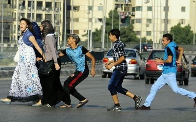 In this Aug. 20, 2012 file photo, an Egyptian youth, trailed by his friends, gropes a woman crossing the street with her friends in Cairo, Egypt. (AP/Ahmed Abd El Latif, El Shorouk Newspaper)