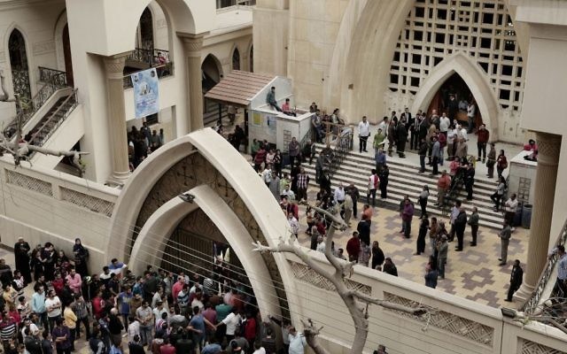 People gather outside the St. George's Church after a deadly suicide bombing, in the Nile Delta town of Tanta, Egypt, Sunday, April 9, 2017. (AP Photo/Nariman El-Mofty)