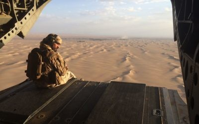 In this Sept. 17, 2015 photo, an Emirati gunner watches for enemy fire from the rear gate of a United Arab Emirates Chinook military helicopter flying over Yemen. . (AP Photo/Adam Schreck)