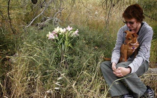Kay Wilson, who survived a stabbing attack as she was hiking in the forest near Jerusalem a few months ago, sits with her dog Peanut at the site of the stabbing, April 21, 2011. Wilson's friend Kristine Luken was killed in the attack which was committed by Ayad Fatafta and Kifah Ghanimat on December 18, 2010. (Miriam Alster/FLASH90)