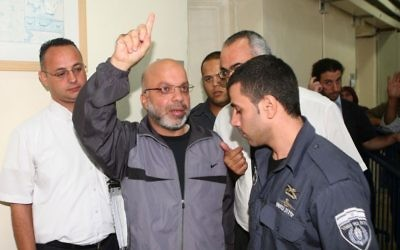 Ahmed Attoun is escorted by police as he leaves the Jerusalem's Magistrate's Court on October 3 2011. (Sliman Khader/FLASH90)