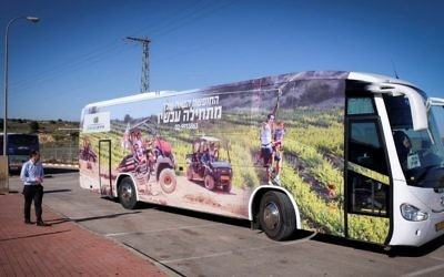 Illustrative: A tour bus with an advertisement encouraging tourists to travel to the West Bank settlement bloc of Gush Etzion, January 6, 2015. (Gershon Elinson/Flash90)