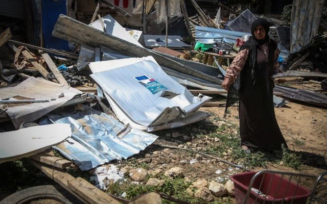 Illustrative: A Bedouin woman inspects the damage of their home after an Israeli bulldozer had demolished the house of the Dahouk family in the Bedouin community of Khan Al Ahmar, in the West Bank east of Jerusalem, on April 7, 2016. (Flash90)