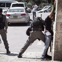 Illustrative: A Border Police officer frisks a Palestinian man in front of Damascus Gate in Jerusalems Old City on September 20, 2016. (Sebi Berens/Flash90)