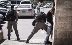 An Israeli Border Police officer frisks a Palestinian man in front of Damascus Gate in Jerusalem's Old City on September 20, 2016 (Sebi Berens/Flash90)