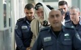 Rabbi Eliezer Berland covers himself with his talit (prayer shawl) at the Jerusalem Magistrate's Court during his trial for sexual assault charges on November 17, 2016. (Yonatan Sindel/Flash90