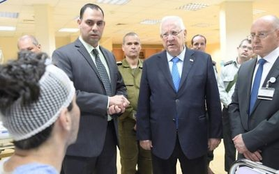 President Reuven Rivlin visits wounded Syrians being treated at a hospital in the northern city of Nahariya on April 9, 2017. (Amos Ben Gershom/GPO)