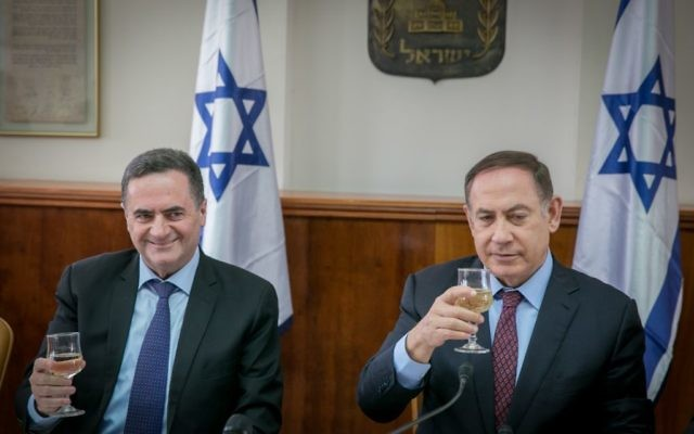 Yisrael Katz, left and prime minister Benjamin Netanyahu raise a toast for the Jewish holiday of Passover during the weekly cabinet meeting at the prime minister office in Jerusalem, on April 9, 2017. (Ohad Zweigenberg/POOL)
