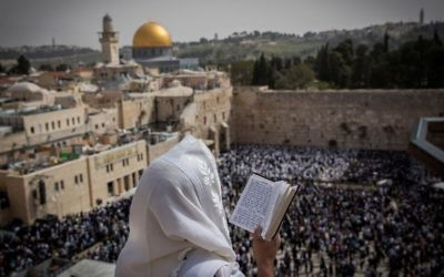 Illustrative: A Jewish man covers himself with a prayer shawl while praying near the Western Wall in Jerusalem's Old City during the Passover priestly blessing on April 13, 2017. (Yonatan Sindel/Flash90)