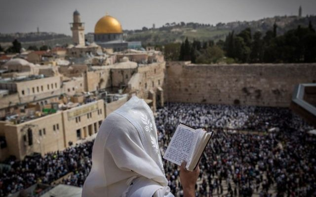 A Jewish man covers himself with a prayer shawl while praying near the Western Wall in Jerusalem's Old City during the Passover priestly blessing on April 13, 2017. (Yonatan Sindel/Flash90)