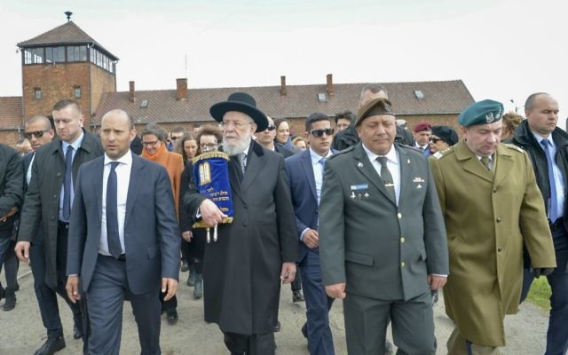 Education Minister Naftali Bennett, left, Rabbi Meir Lau, center, and IDF chief of staff Gadi Eisenkot participating in the March of the Living at the Auschwitz-Birkenau camp in Poland, as Israel marks annual Holocaust Memorial Day, April 24, 2017. (Yossi Zeliger/Flash90)